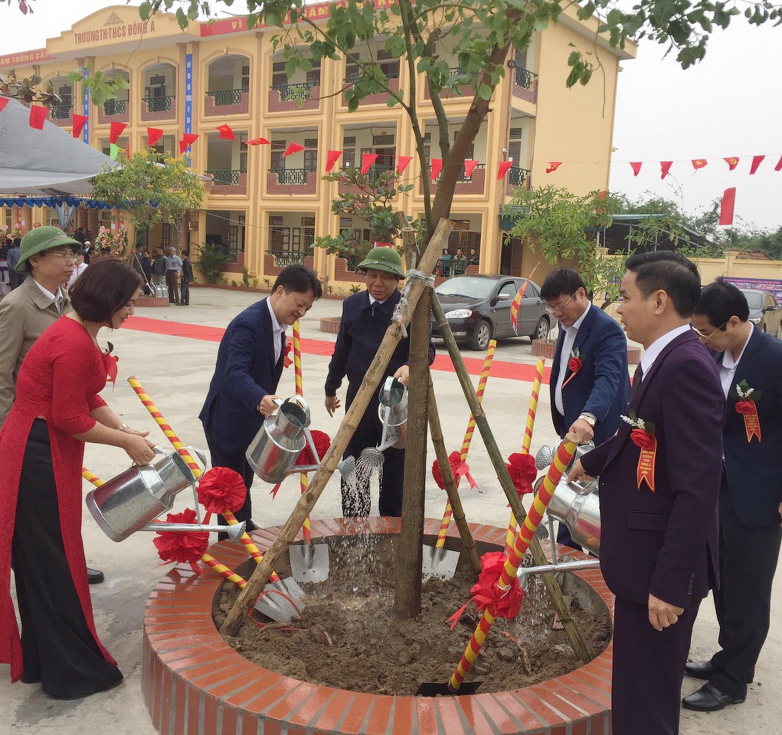 Các vị đại biểu tham gia trồng cây lưu niệm, tạo màu xanh cho trường